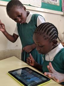 Liz Mwikali (standing) signing along with a classmate with the help of the interpreter in the digital accessible textbook