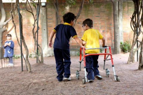 Two boys, one with a walker in a playground