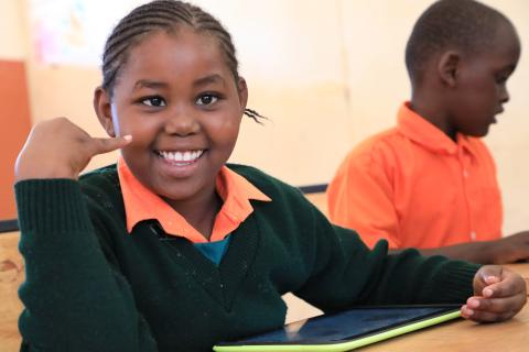Girl with intellectual disability smiling while using a tablet in the classroom.