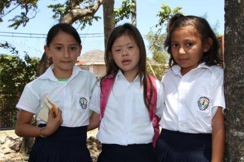 Three school girls stand outside