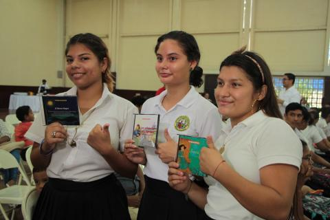 Three school girls holding the video book CDs
