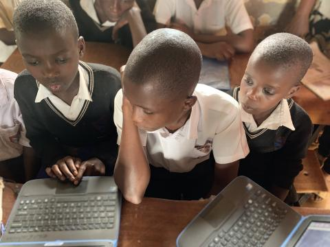 Three boys in a school in Uganda using laptops