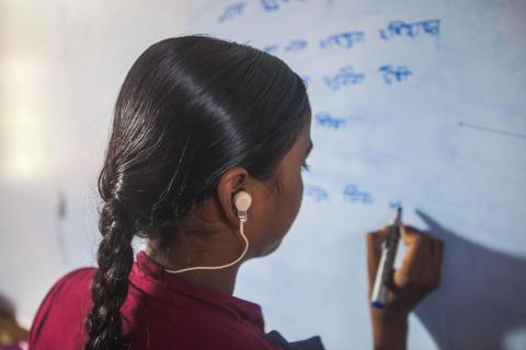Sulekha, a girl with a hearing impairment, writes on a white board during a class at a bridge school