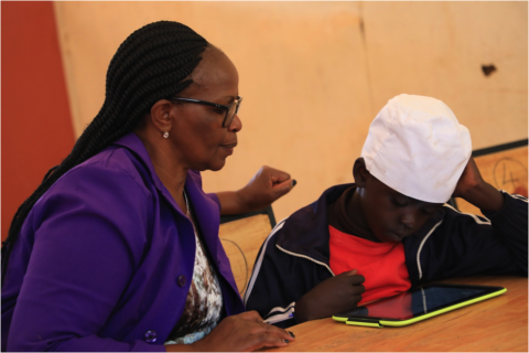 Teacher Jane Njoroge looks on as Frank from Mugumoini Primary School in Thika Town uses his digital tablet
