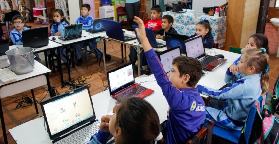 Classroom with children on laptops using the ADT, one child raises his hand.